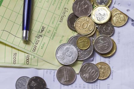 インドネシア ルピアとシンガポール ドル硬貨、計算機上での請求書と支払の領収書計算資料のイラスト表示平面レイアウト