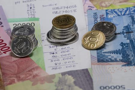 コイン、紙幣、および手書きの費用計算で示されたお金と支払いを過ごす