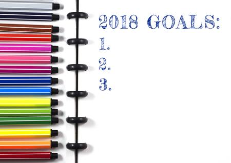 2018 カラーペン、トップビューを持つ白いスケッチブック上の目標テキスト