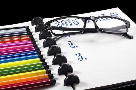 2018 カラーペンと眼鏡を使用した白いスケッチブックの目標テキスト 写真素材