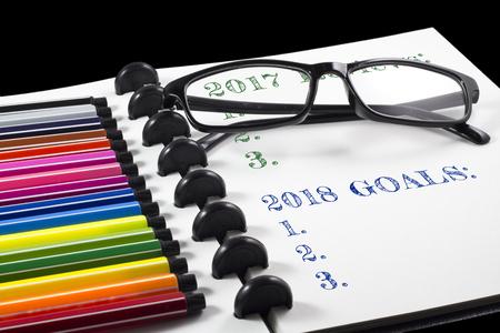 2017 レビューと 2018 目標は、カラー ペンと眼鏡と白いスケッチブック上のテキスト