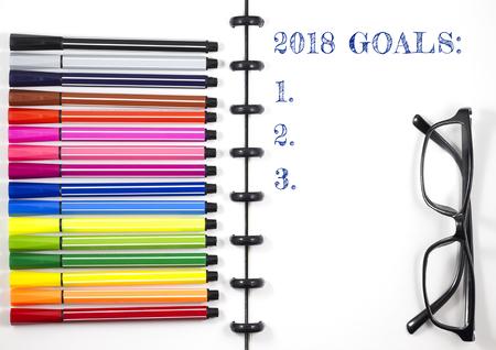 2018カラーペンと眼鏡、トップビューフラットレイと白いスケッチブック上の目標テキスト