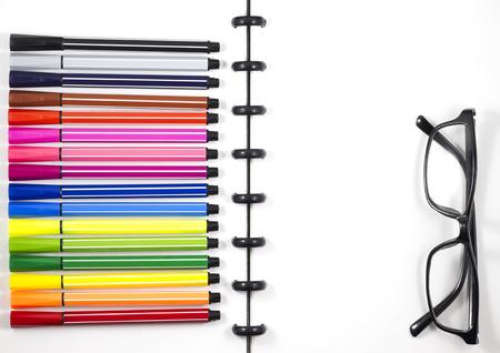 ビジネステンプレート用のカラーペンと眼鏡を備えた白い空白のスケッチブック、トップビューフラットレイ