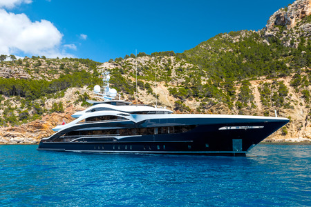 Luxury large sea or mega motor yacht in the blue sea near the mountains.