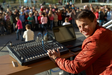 audio mixer: The young smiling man works as the dj