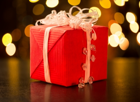 Christmas gift with bow on defocused lights background photo