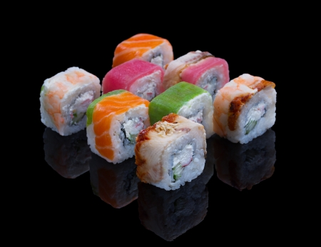 Sushi set with avocado, shrimp, tuna, salmon and eel on black background Stock Photo