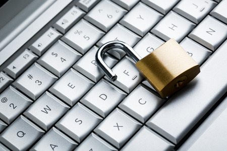 Unlocked Padlock on laptop keyboard, close-up Standard-Bild