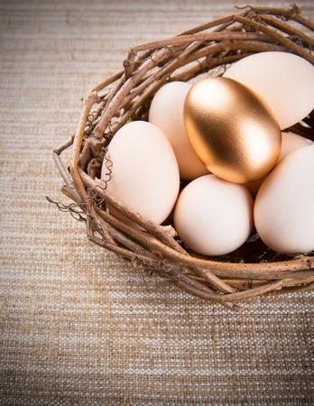 retirement nest egg: Eggs in nest on linen fabric close-up