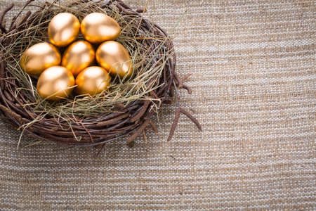 Gold eggs in nest from hay close-up