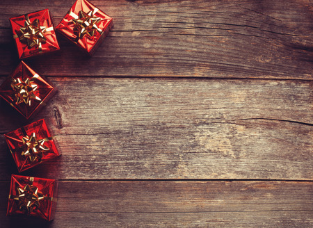 close up image: Christmas Red Gift Boxes with ribbon on rustic wood board