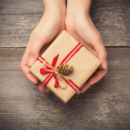 small paper: Hands holding gift box with pine cone
