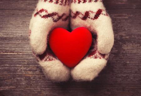 Las manos en los guantes de la celebración de corazón rojo Foto de archivo