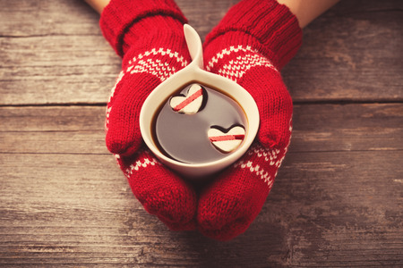 women holding cup: Hands in mittens holding hot cup of coffee with marshmallow hearts on wooden background Stock Photo