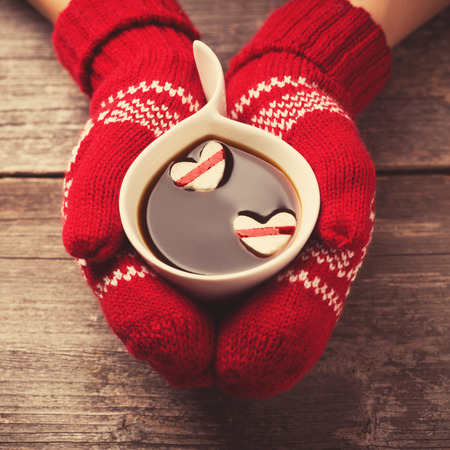 woman drinking milk: Hands in mittens holding hot cup of coffee with marshmallow hearts on wooden background Stock Photo