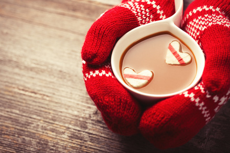 human milk: Hands in mittens holding hot cup of coffee with marshmallow hearts on wooden background Stock Photo