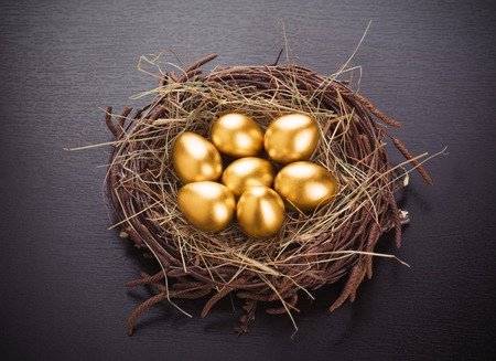 Gold eggs in nest from hay on table Foto de archivo