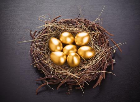 nido de pajaros: Los huevos de oro en nido de heno en la mesa Foto de archivo