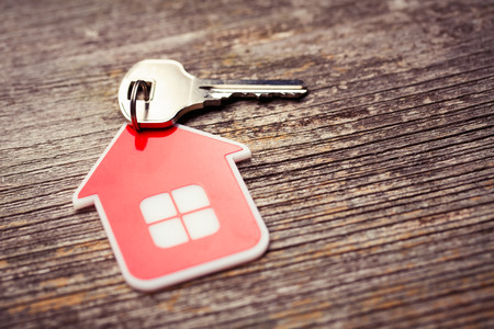 Key and Red House on Wood background Stockfoto