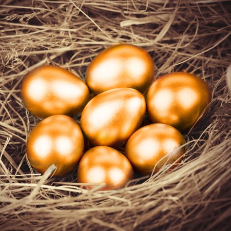 gold eggs: Gold eggs in nest from hay close-up