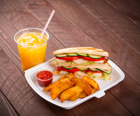 Refreshments: Sandwich, potatoes and juice on wood background