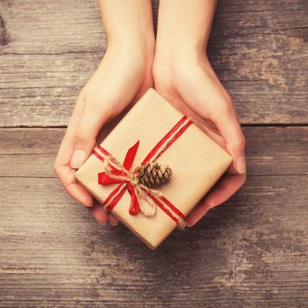 traditional gifts: Hands holding gift box with pine cone