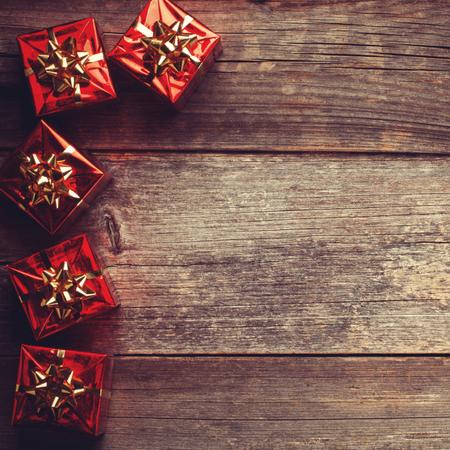 madera rústica: Navidad rojo cajas de regalo con la cinta en el tablero de madera rústica Foto de archivo