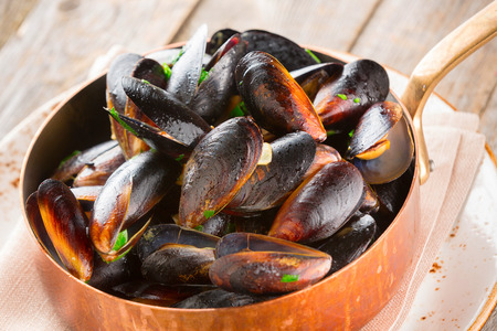Mussels cooked in wine sauce with herbs in a frying pan on wood background.