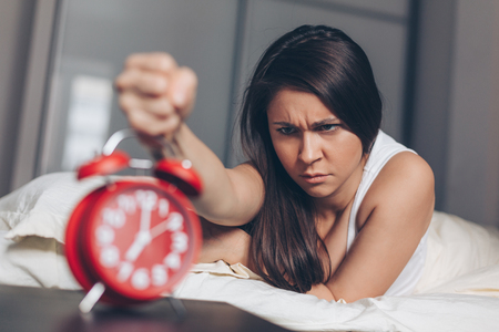 Angry young woman kill off alarm clock by fist on the bed in the morning. Awakening of the sleeping woman. Focus on woman. Stock Photo