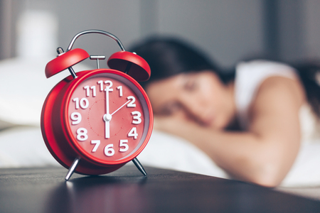 Alarm clock closeup and young sleeping woman in bedroom at home
