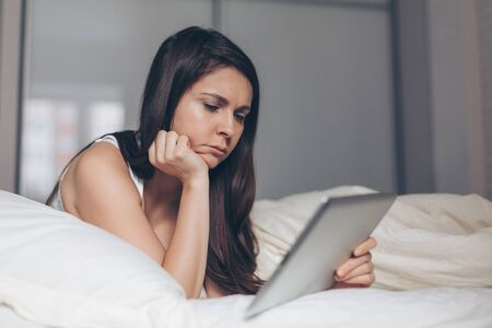 Sad girl looks into tablet in hands on bed