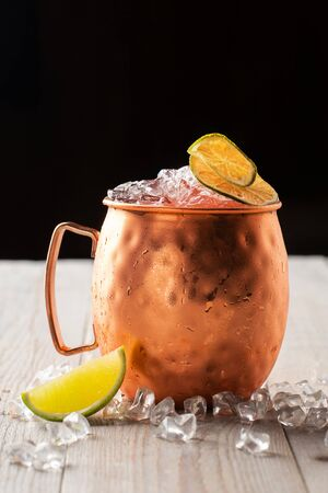 Moscow Mule cocktail in a Copper Mug garnished with dried Lime and ice on black background