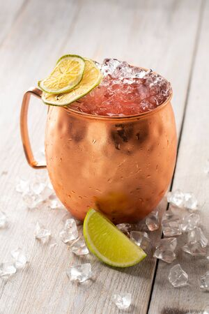 Moscow Mule cocktail in a Copper Mug garnished with dried Lime and ice on white wooden table Stock Photo
