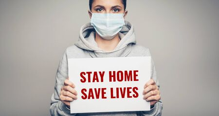 Studio portrait of young woman wearing a face mask holding board with stay home save lives tex on gray background. Coronavirus pandemic virus concept
