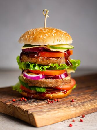Big royal tasty burger, hamburger, cheeseburger with two cutlets, tomatoes, cucumber, salad, onion, cheese and sauce on wooden cutting board on grey background