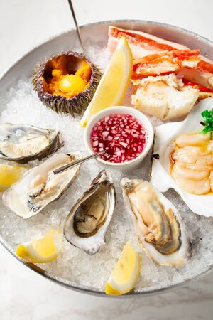 Large dish with fresh assorted seafood on ice - oysters, sea urchin, scallops and crab. Close up view of seafood with lemon slice and sauce. Seafood on plate with crushed ice in restaurant