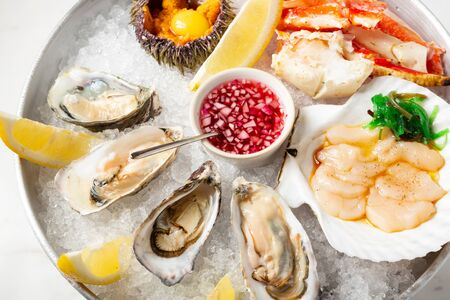 Large dish with fresh assorted seafood on ice - oysters, sea hedgehog, scallops and crab. Close up view of seafood with lemon slice and sauce. Seafood on plate with crushed ice in restaurant