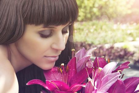 美しい少女の花を見て、香りクローズ アップを吸い込む 写真素材