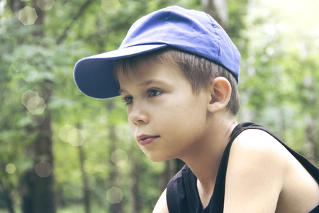 The boy in a cap sits in the woods and looks out into the distance