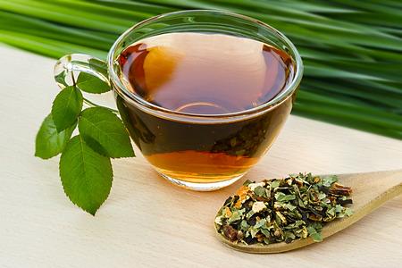 tea spoon: Cup of tea tea with dry herbal tea in wooden spoon on the side.