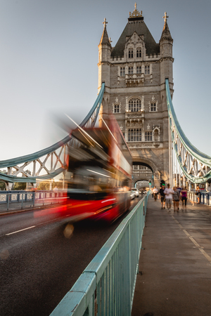A red bus crossing the tower bridge