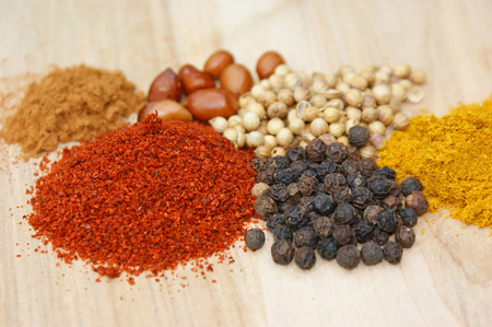 peppercorn: spicies on a wooden plate: chilli, pepper, coriander, curry, cinnamon, nuts