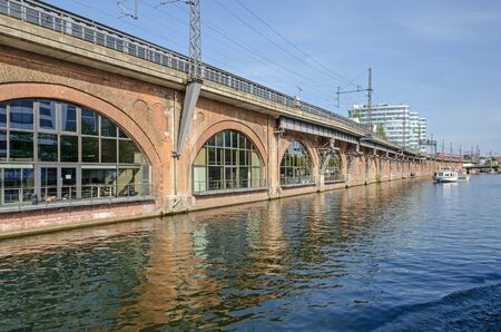 A city railway Viaduct with incoming train, tourist boat and the Triassic Towers at the background Reklamní fotografie