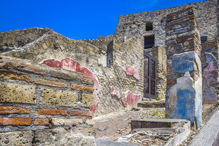 Part of the colored brick wall and street in Pompeii, Naples, Italy. The ruins of the ancient city, excavations of Pompei scavi.