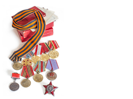 Concept May 9, victory USSR in the Second World War - Order of the Red Star, medals for liberation of Berlin, Warsaw, for valor and merit and St. Petersburg. Georges ribbon, on white background, with place for text Stock Photo