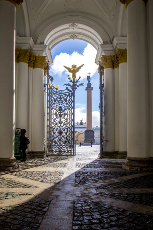 View of Palace Square with Alexandrian column from the Hermitage Museum with wrought-iron gates and golden double-headed eagle, rays of sun Petersburg, Russia