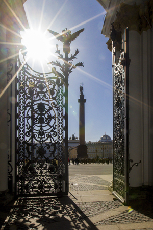 View of Palace Square with Alexandrian column from arch of Hermitage Museum with wrought-iron gates and shadow from gate leaf, rays of sun illuminate entrance to Hermitage, St. Petersburg, Russia Standard-Bild