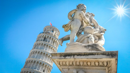 Leaning Tower of Pisa and statue of cherubs winged angels supporting heel of tower and shining fair bright sun with beams at clear blue sky, Pisa, Tuscany, Italy. Stock Photo