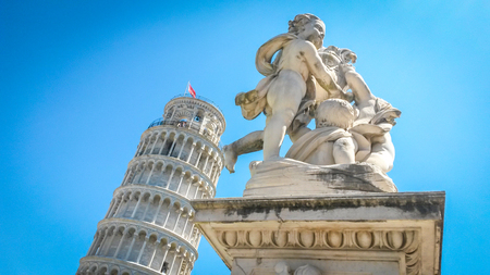 Leaning Tower of Pisa and statue of cherubs winged angels supporting heel of tower, Pisa, Tuscany, Italy. Stock Photo