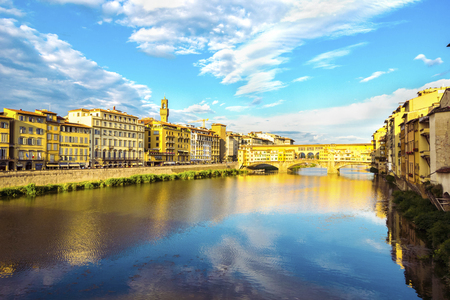 Panoramic view of the Arno River and stone medieval bridge Ponte Vecchio with beautiful reflection of colorful houses and blue sky with porous clouds, Florence, Tuscany, Italy. Archivio Fotografico